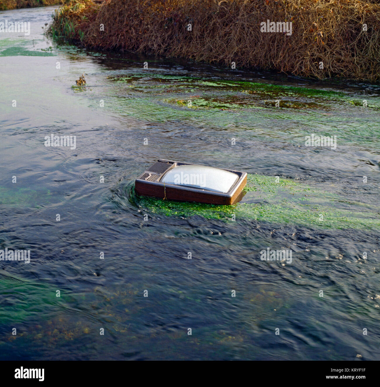 Italy, Lombardy, Provincie of Cremona, Water Pollution, Old TV Dumped in River - Stock Image