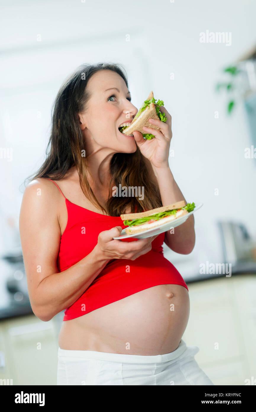 Schwangere Frau isst ein Sandwich - pregnant woman eats a sandwich Stock Photo
