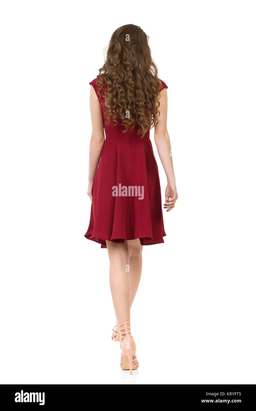 Woman in red dress and high heels is walking. Rear view. Full length studio shot isolated on white. - Stock Image