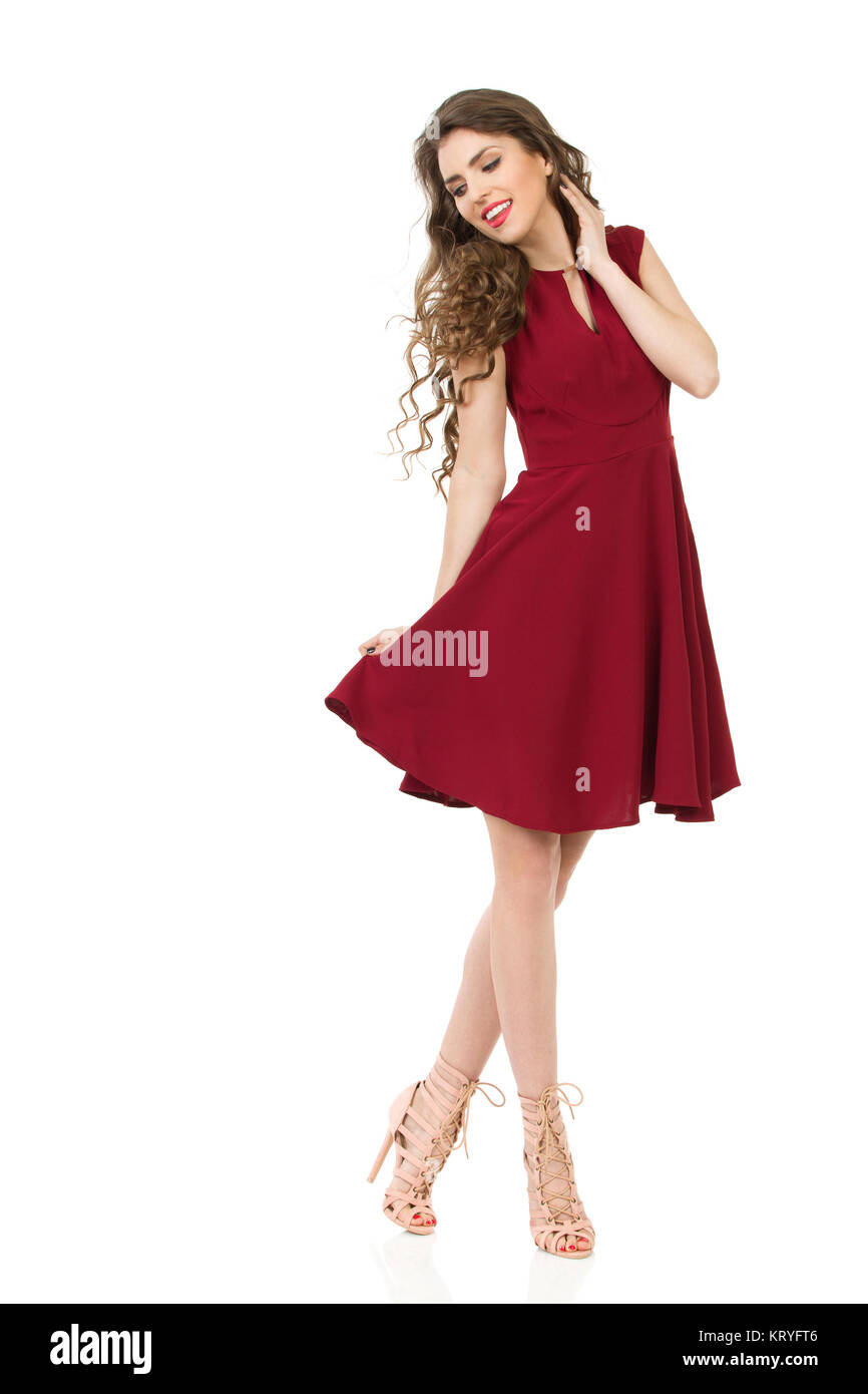 64044b3e11a Young woman in red dress and high heels is standing with legs Stock ...