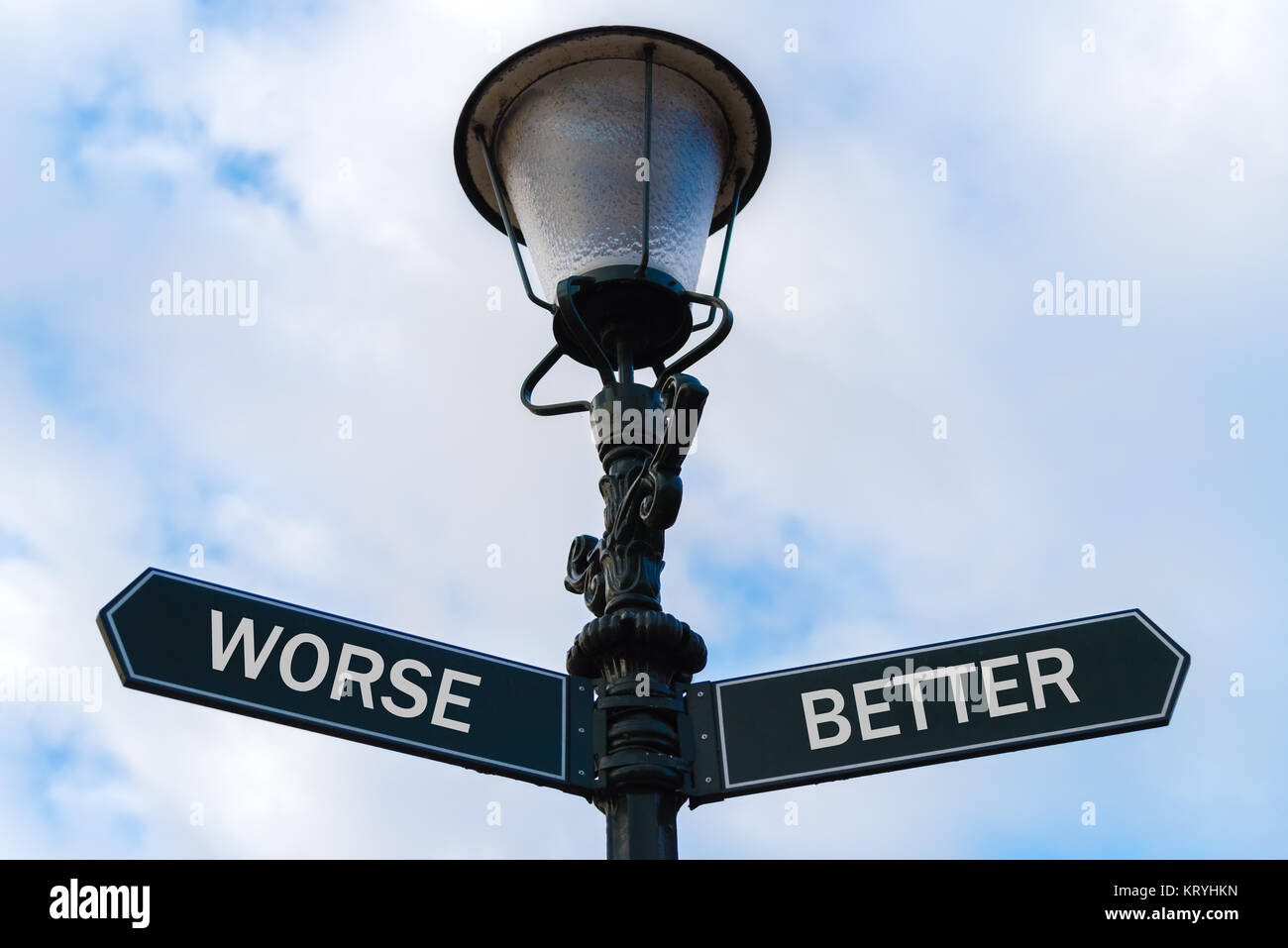 Worse versus Better directional signs on guidepost Stock Photo