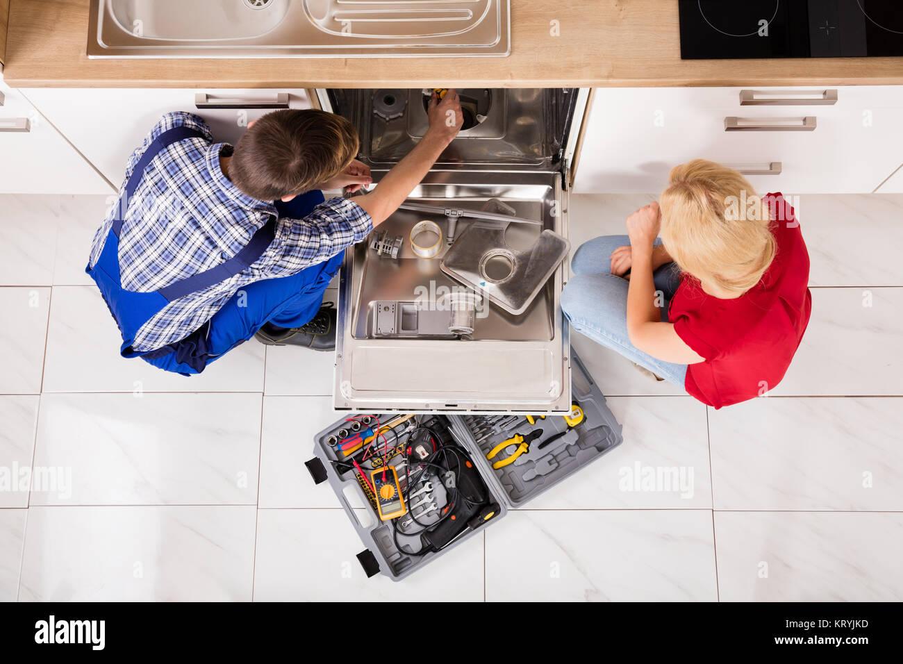 Woman Looking At Repairman Repairing Dishwasher - Stock Image