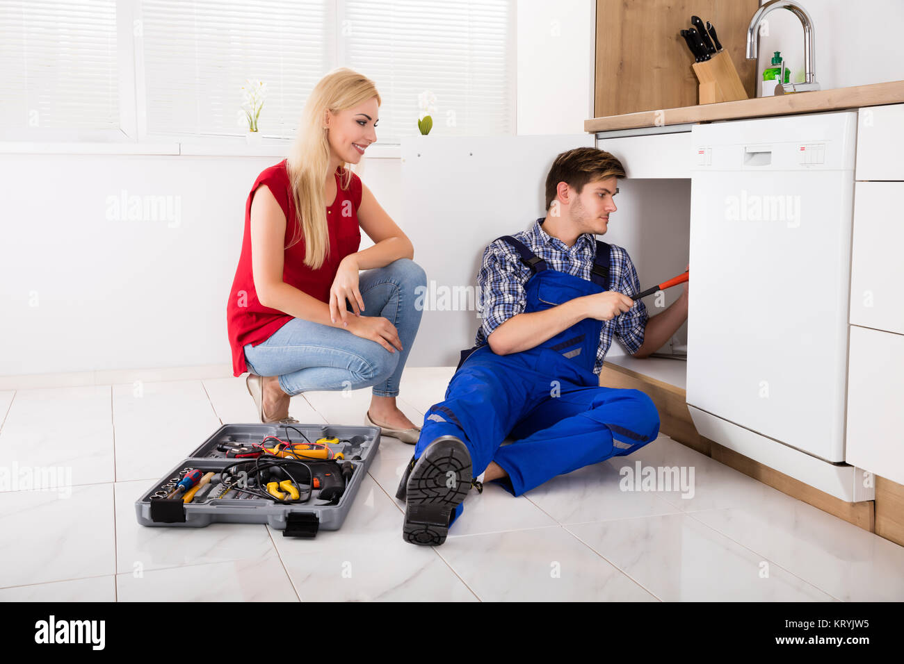 Woman Looking At Male Plumber Fixing Kitchen Sink - Stock Image