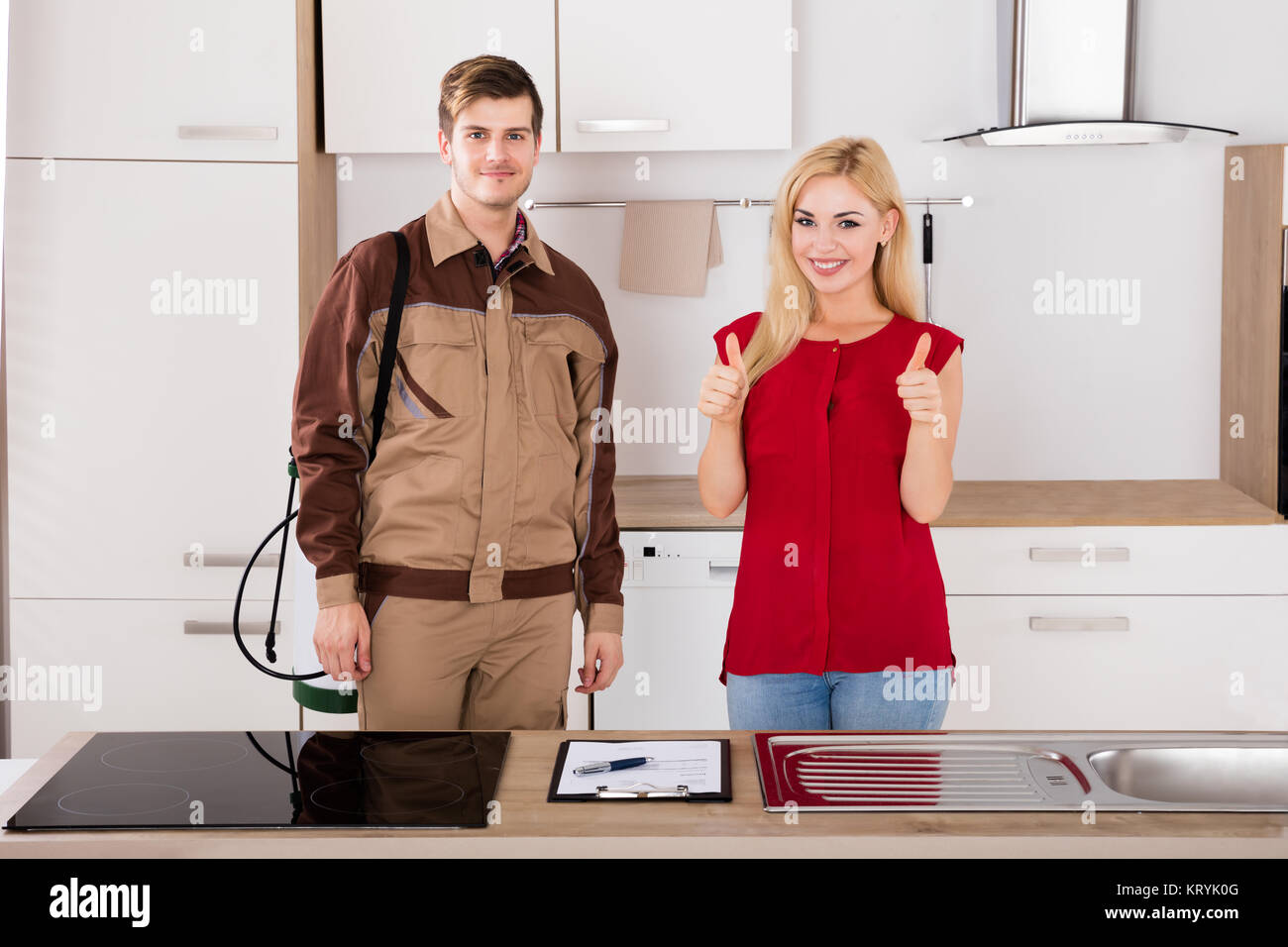 Portrait Of Woman And Pest Control Worker In Kitchen - Stock Image