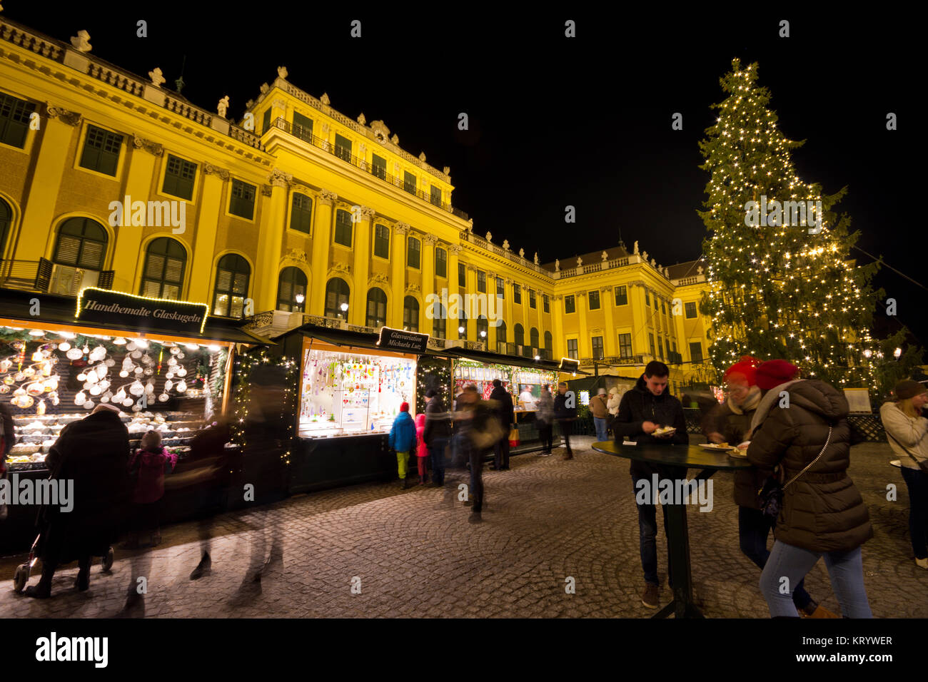 Traditional christmas market with illuminated Schönbrunn palace and fairy lights decorated Christmas tree at - Stock Image