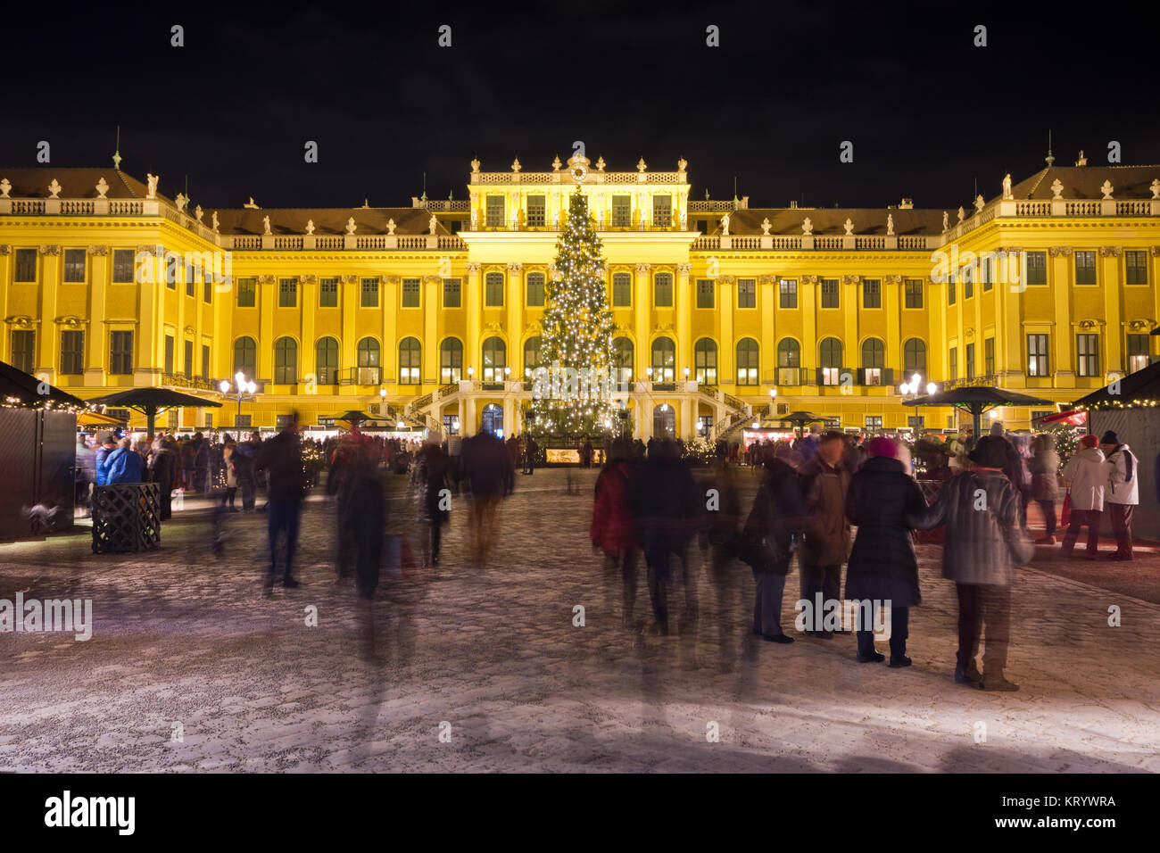 View of illuminated Schönbrunn palace in Christmas time with fairy lights decorated Christmas tree at dusk - Stock Image