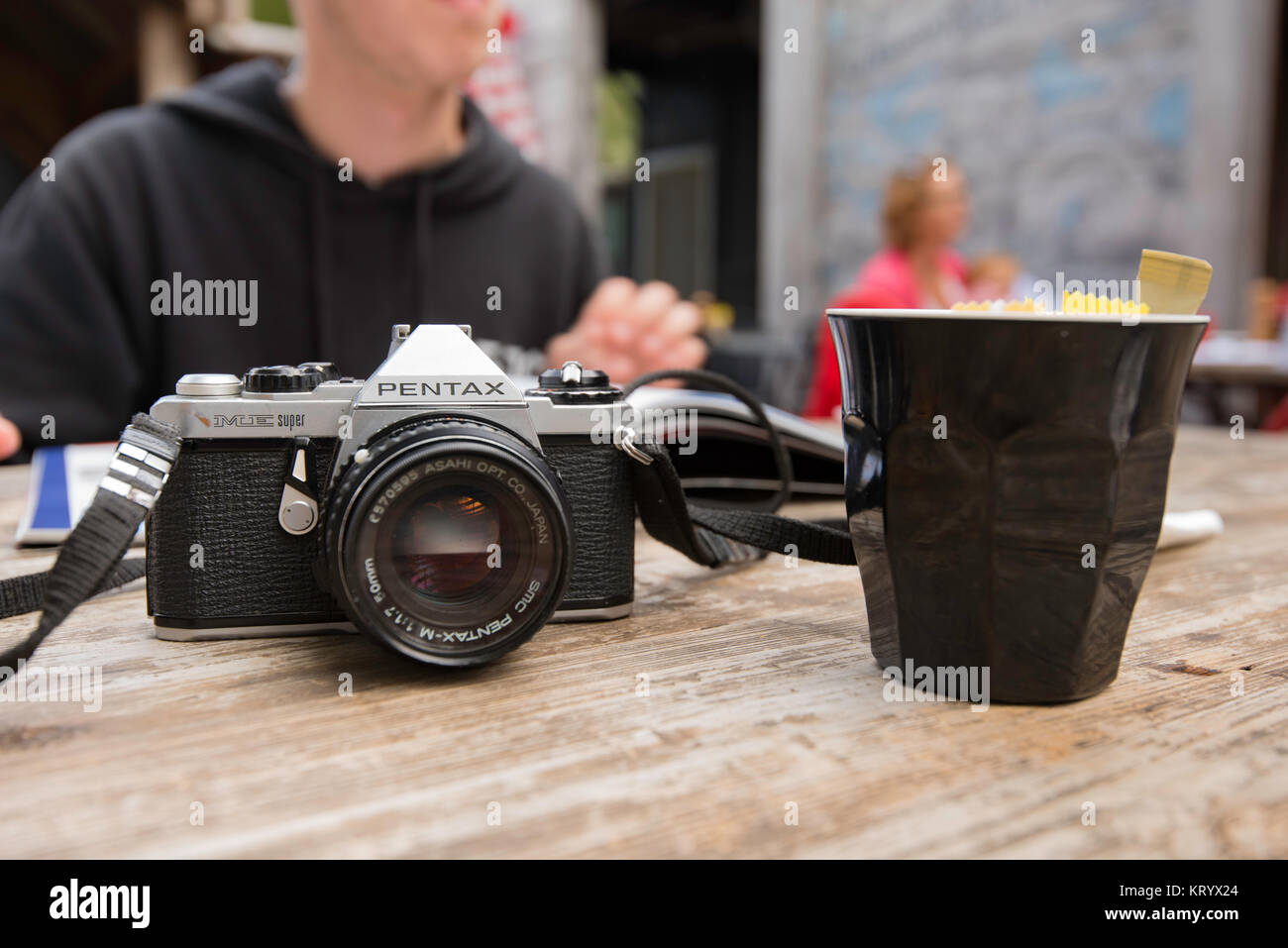 An old 35mm SLR film camera sitting on a table in a coffee shop - Stock Image