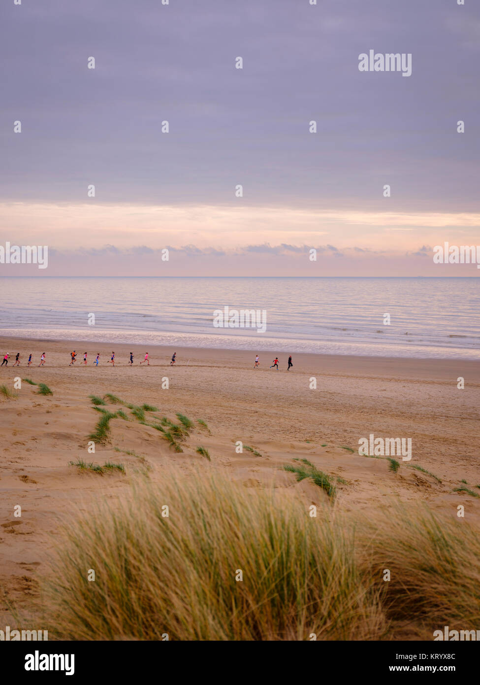 Runners training on Camber beach on a winter morning, East Sussex, UK - Stock Image