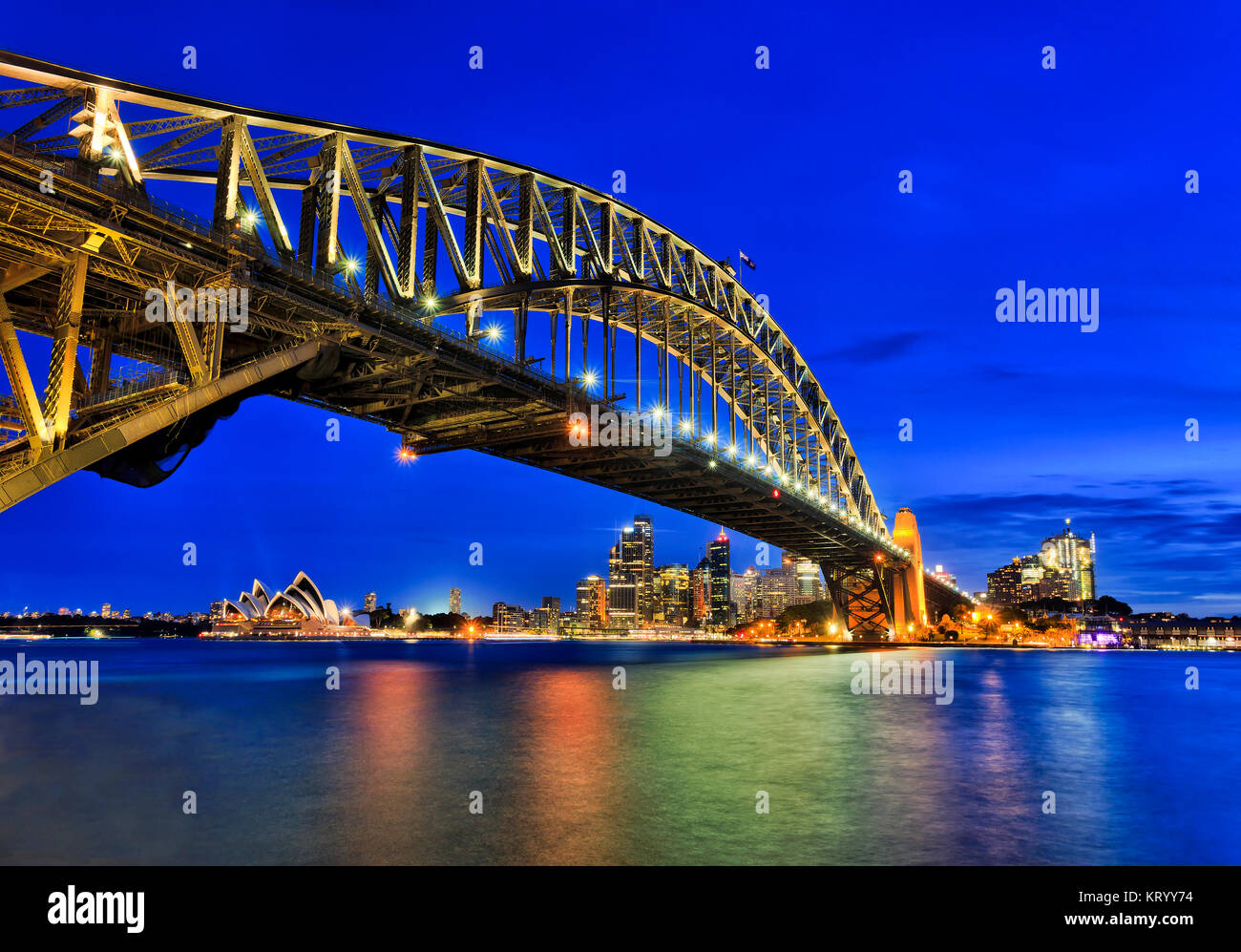 Side view of Sydney Harbour bridge towards city CBD, the Rocks and Circular quay at sunset across blurred reflecting - Stock Image