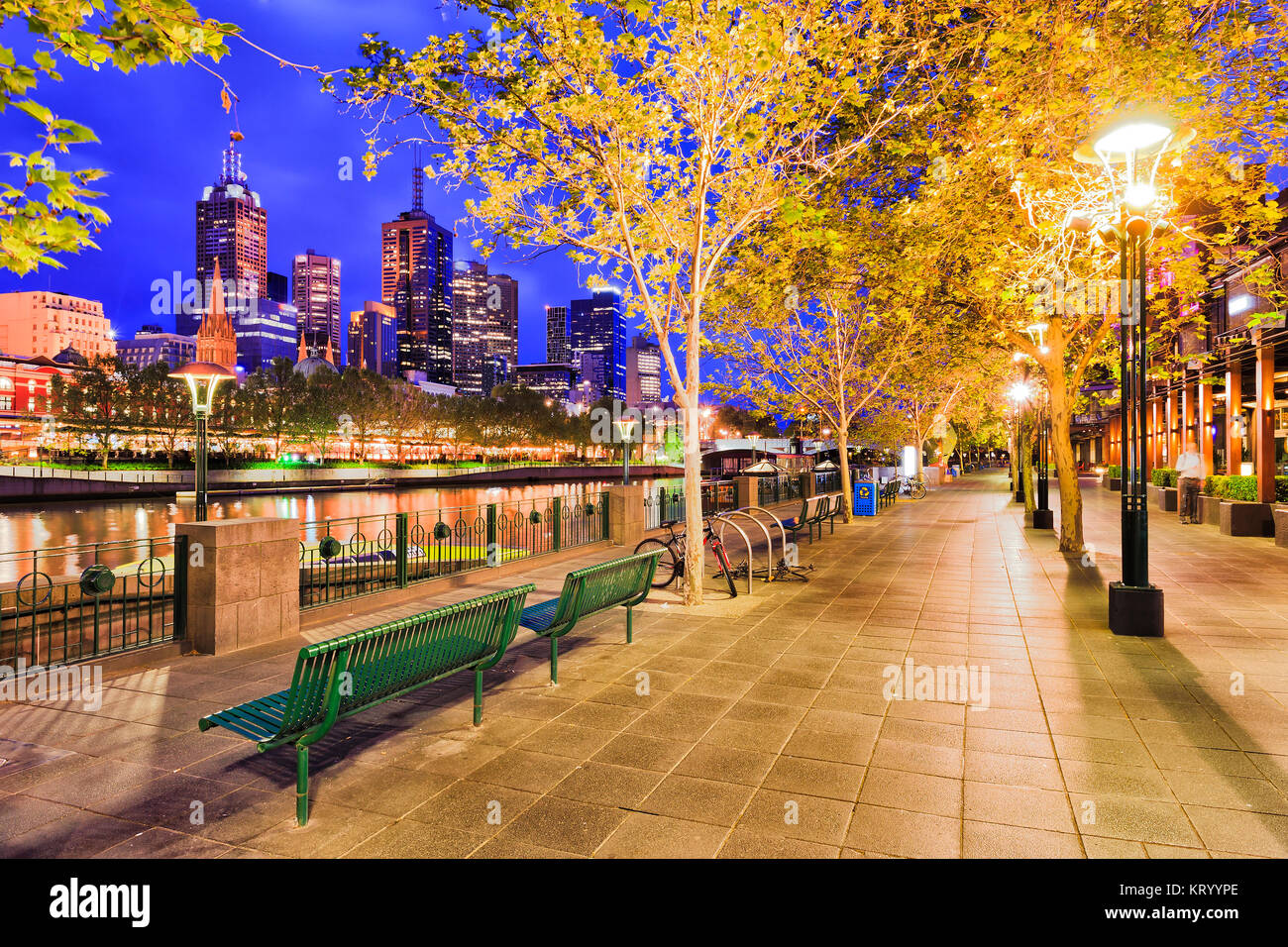 Boardwalk for shoppers on southbank yarra river side in Melbourne city CBD at sunrise under leafy trees and illuminated - Stock Image