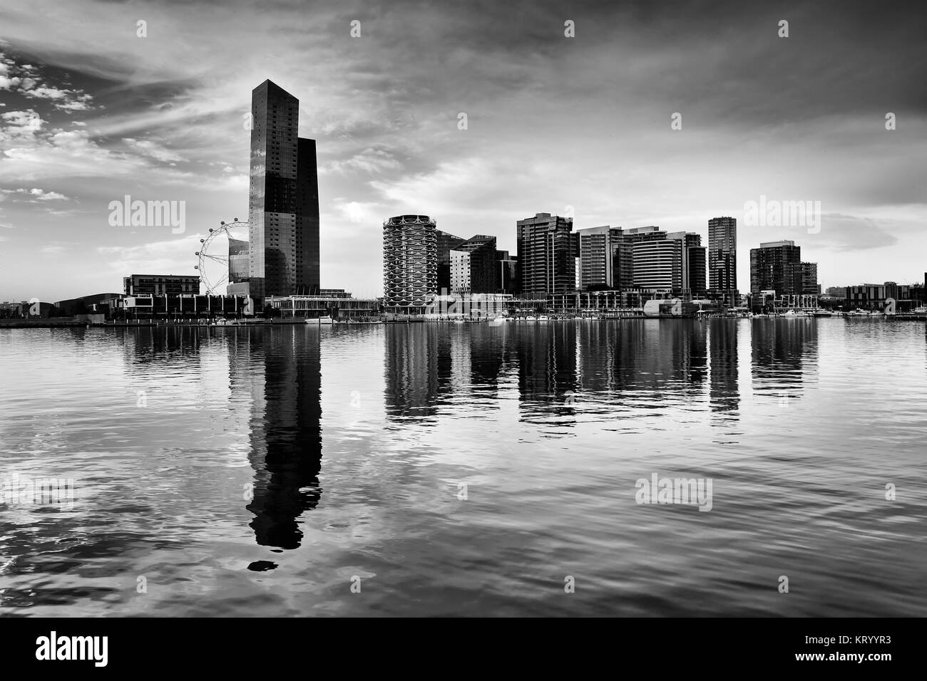 Black white dramatic view of modern Docklands residential high-rise towers and amusement observation wheel reflecting - Stock Image