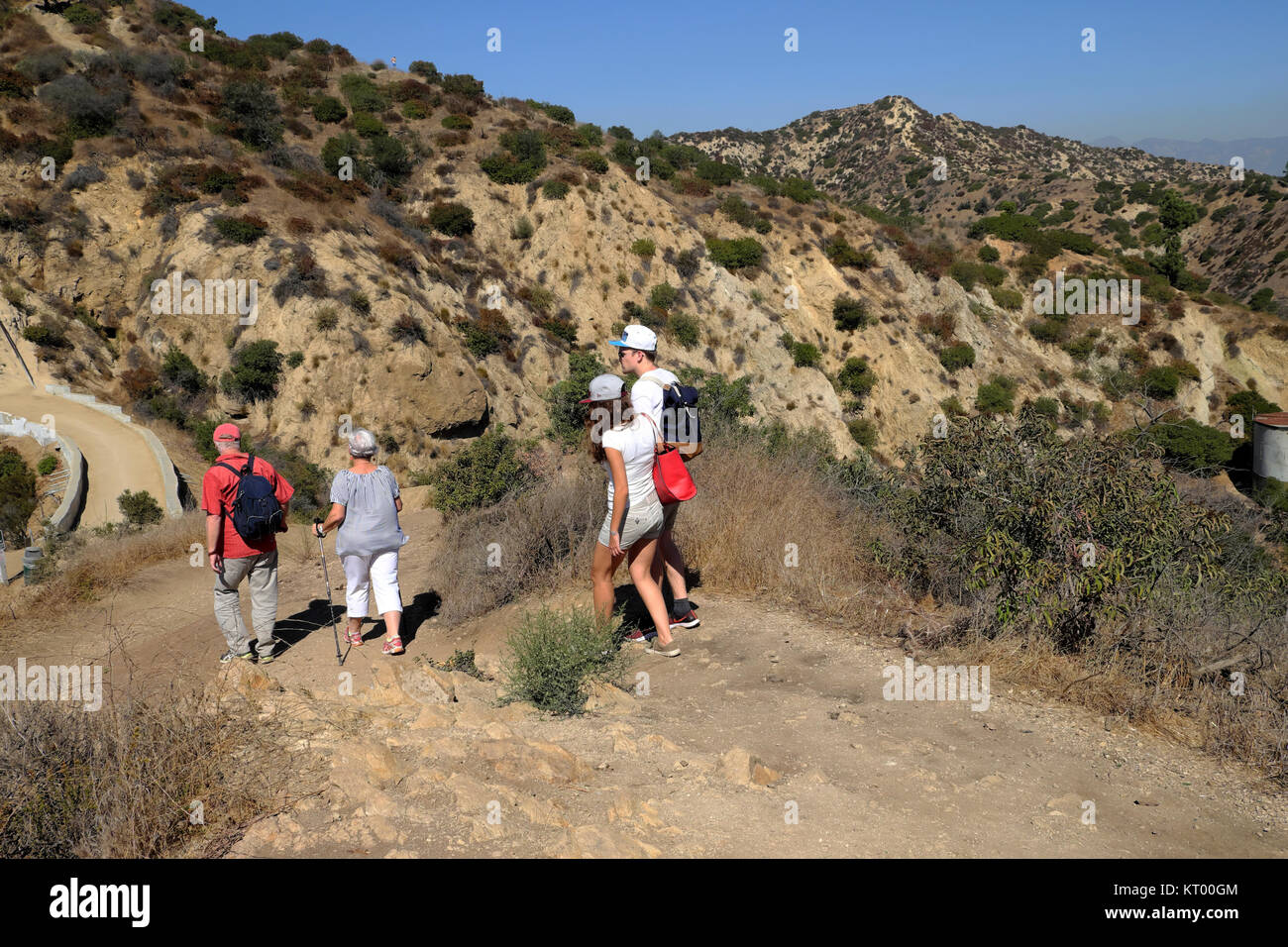 Family walking up the trail to Griffith Park Observatory in Griffith Park hills & cityscape of downtown Los - Stock Image