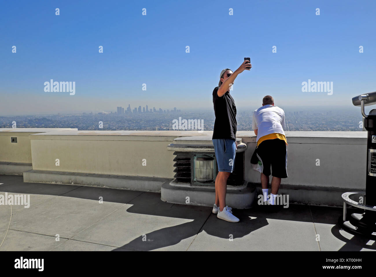 A young man taking a selfie with downtown LA background from Griffith Observatory roof at Griffith Park in Los Angeles, - Stock Image