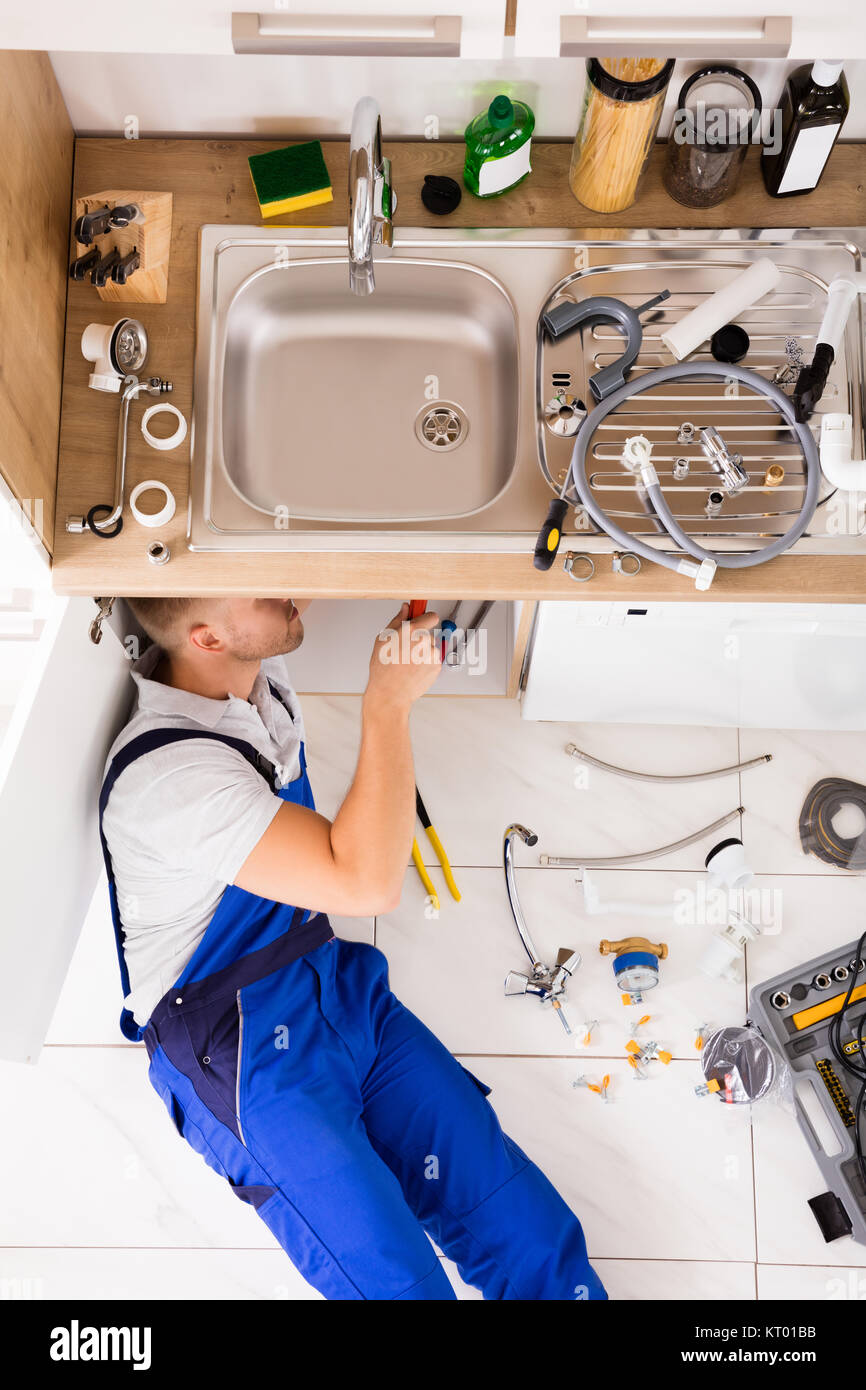 Male Plumber In Overall Fixing Sink Pipe - Stock Image
