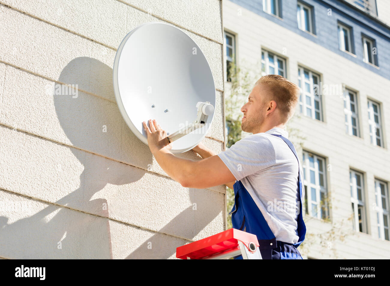 Man Fitting TV Satellite Dish - Stock Image