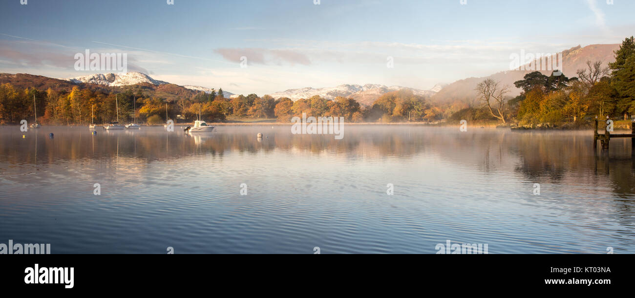 Mist rises from the calm waters of Windermere lake at Ambleside Pier, beside autumn woodland and under thew snow - Stock Image