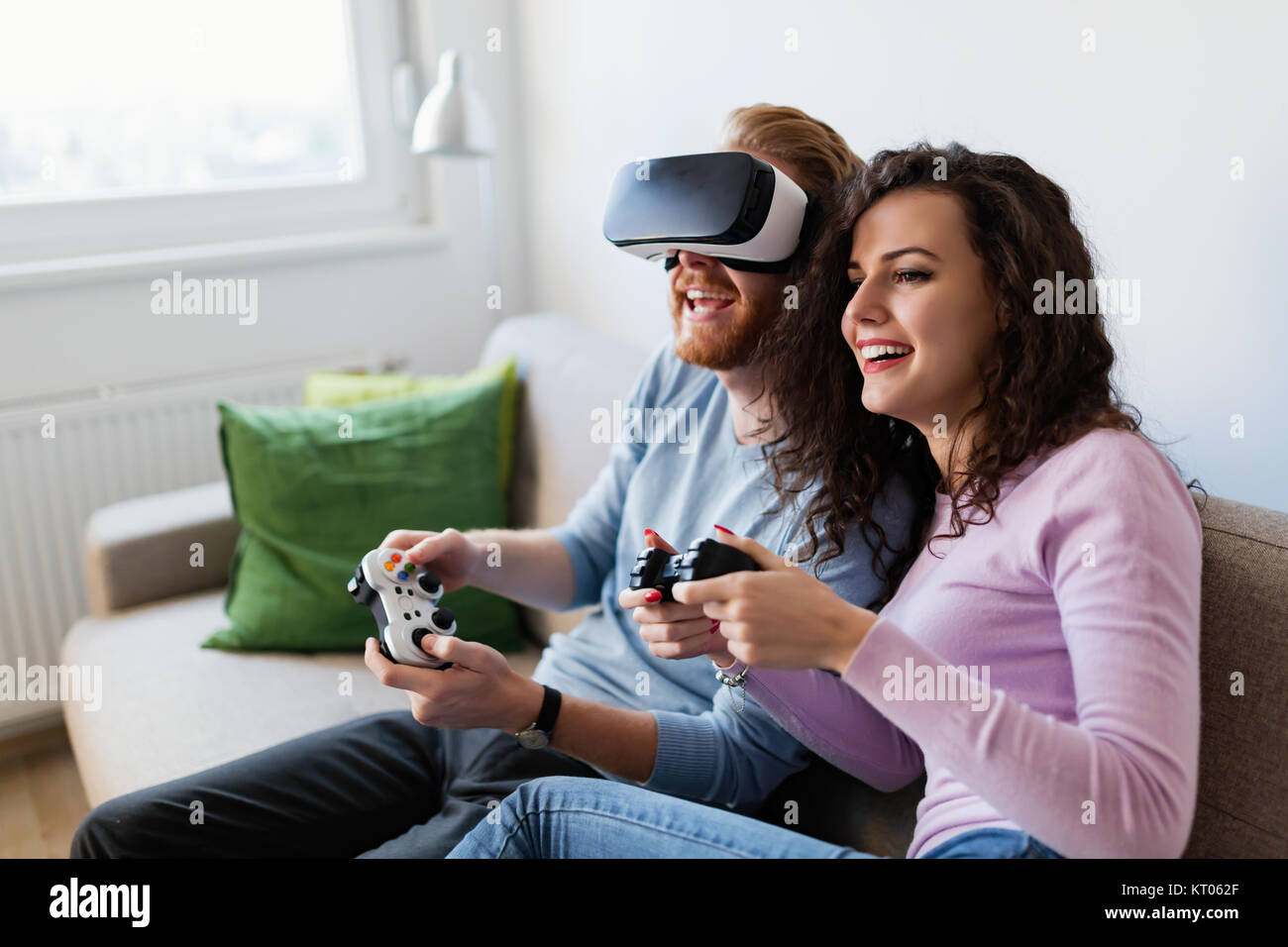f4717a523624 Happy young couple playing video games with virtual reality headsets -  Stock Image