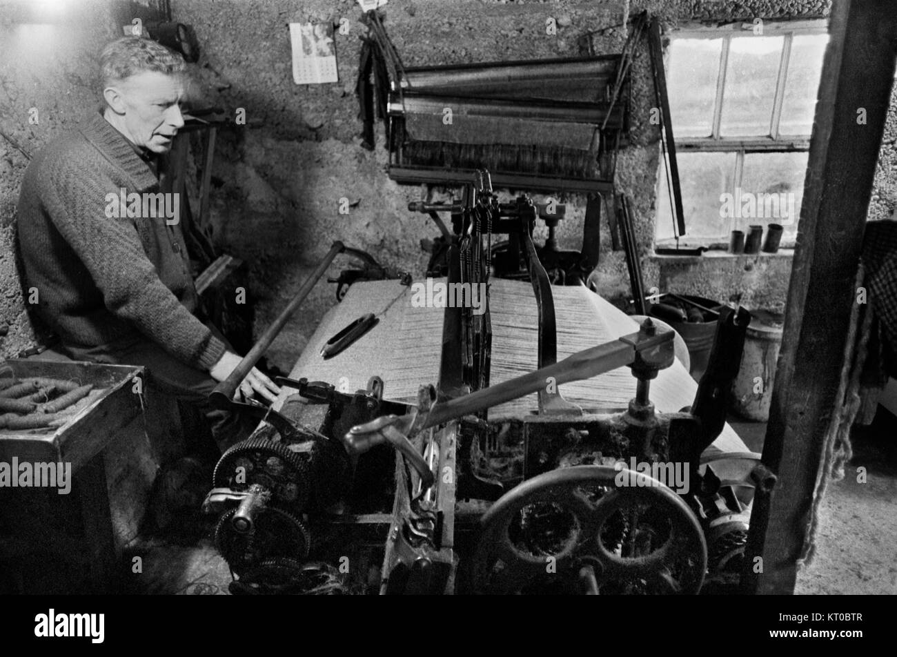 Tweed weaving on old fashioned hand loom weaver at work 1970s, Isle of Lewis Outer Hebrides  Highlands and Islands - Stock Image