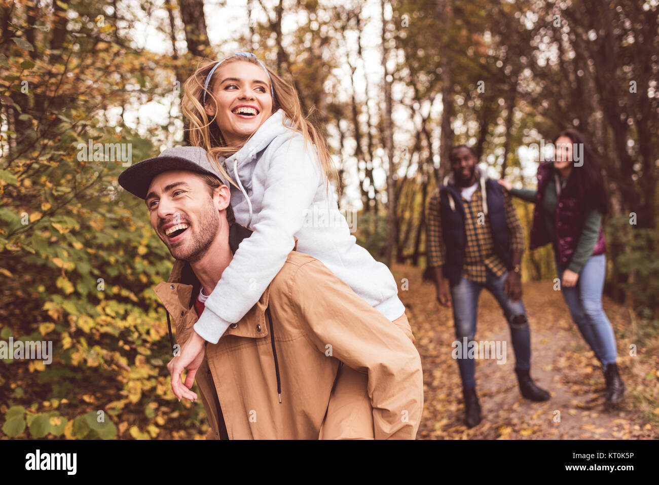 Happy friends having fun in forest Stock Photo