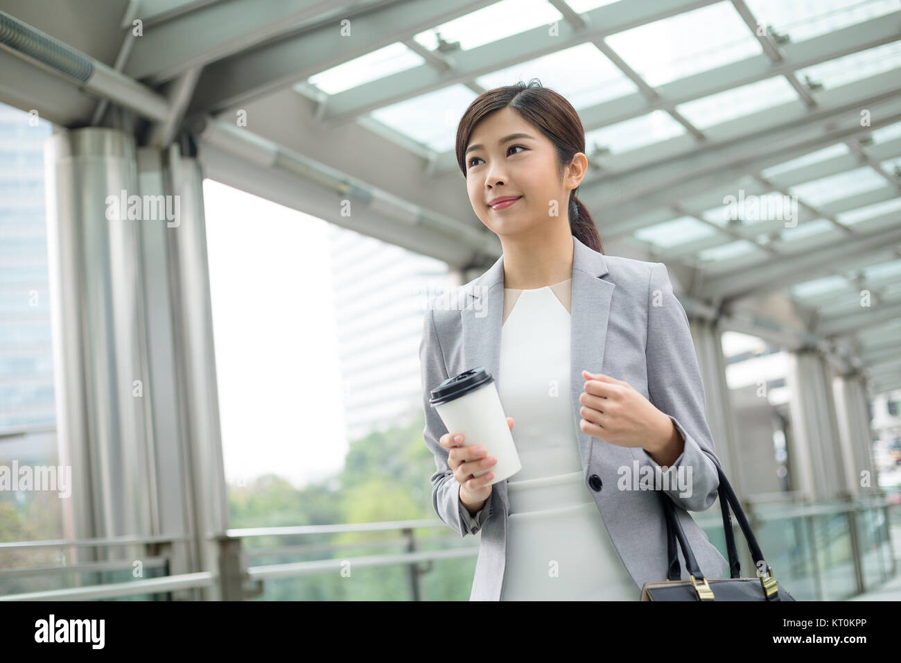 Asian Businesswoman holding a coffee and walking outdoor - Stock Image