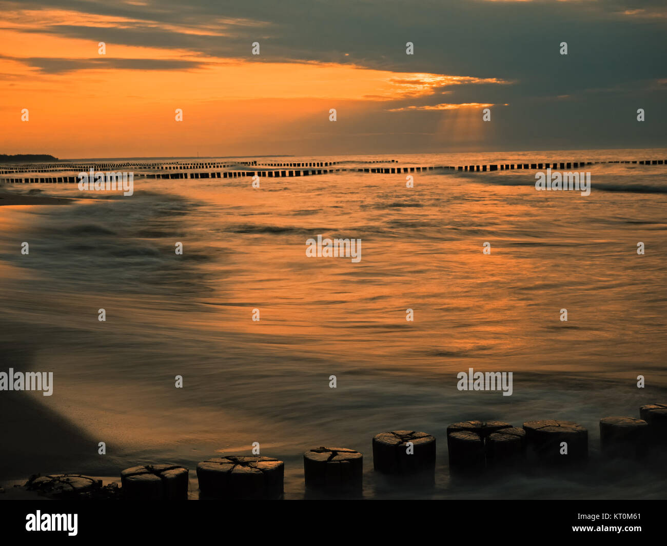 Baltic Sea with breakwaters at sunset - Stock Image