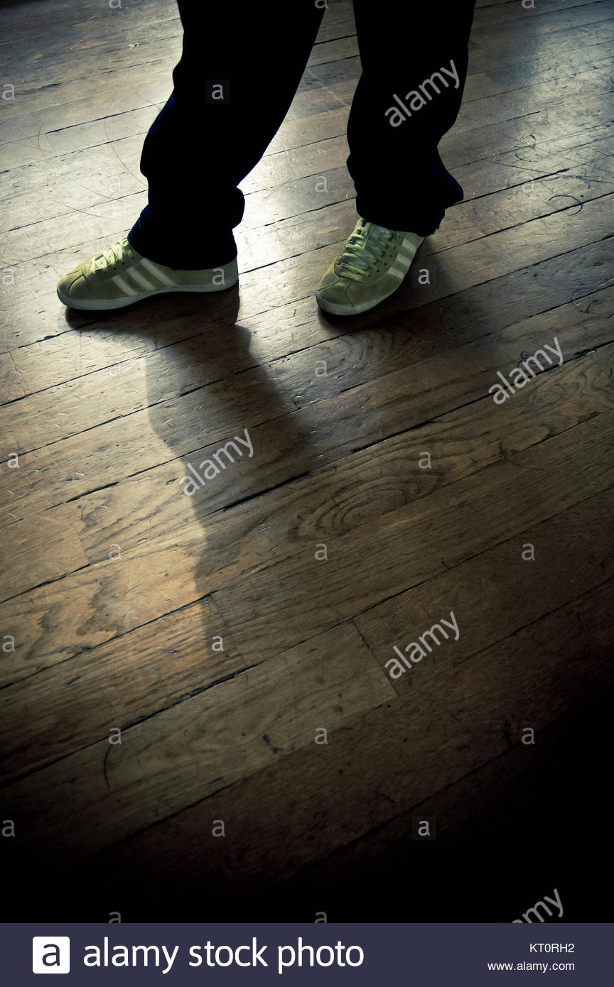 a boy legs and sneakers standing on wood planks - Stock Image