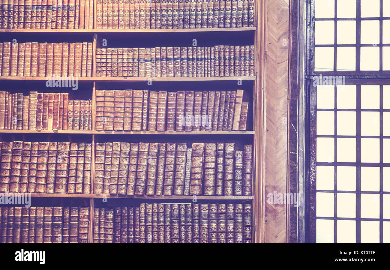 Vintage toned old books on wooden shelves, education concept background. - Stock Image