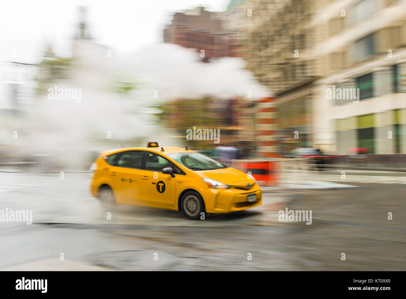A panning shot of a yellow taxi cab driving along a street in lower Manhattan, New York, USA - Stock Image