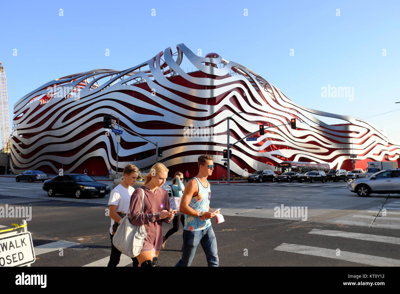 Group of young teenage tourists walking along Wilshire Blvd. past Petersen Automotive Museum building in Los Angeles, - Stock Image