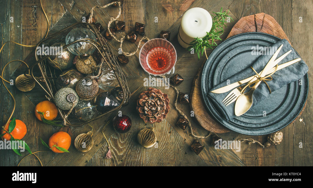 Christmas or New Years eve holiday table setting. Flat-lay of plates, silverware, champaigne in glass, candle and - Stock Image