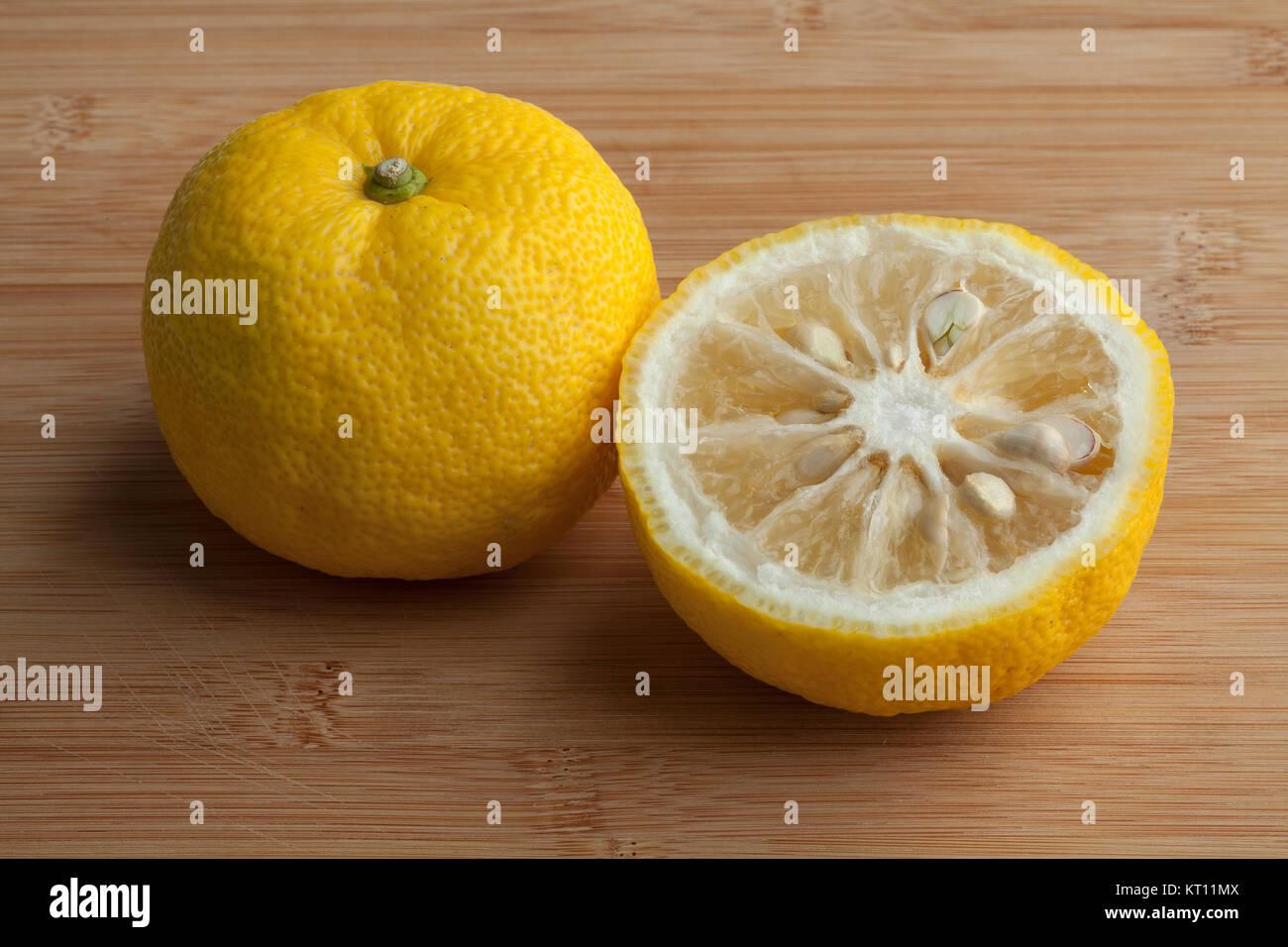 Fresh yellow whole and half Japanese Yuzu fruit - Stock Image