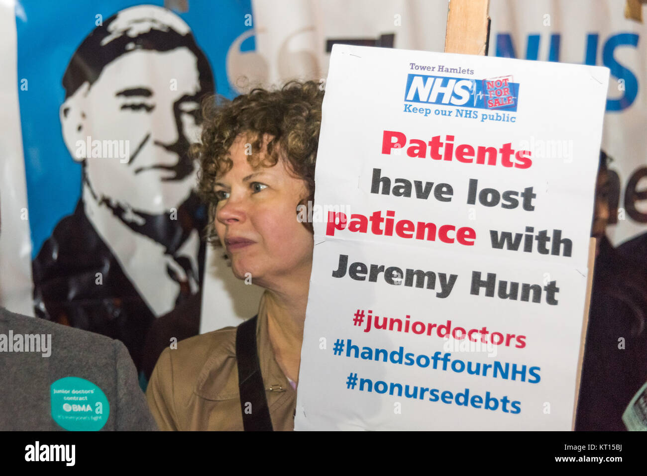 A woman in front of the image of Nye Bevan holds a poster 'Patients have lost patience with Jeremy Hunt' - Stock Image