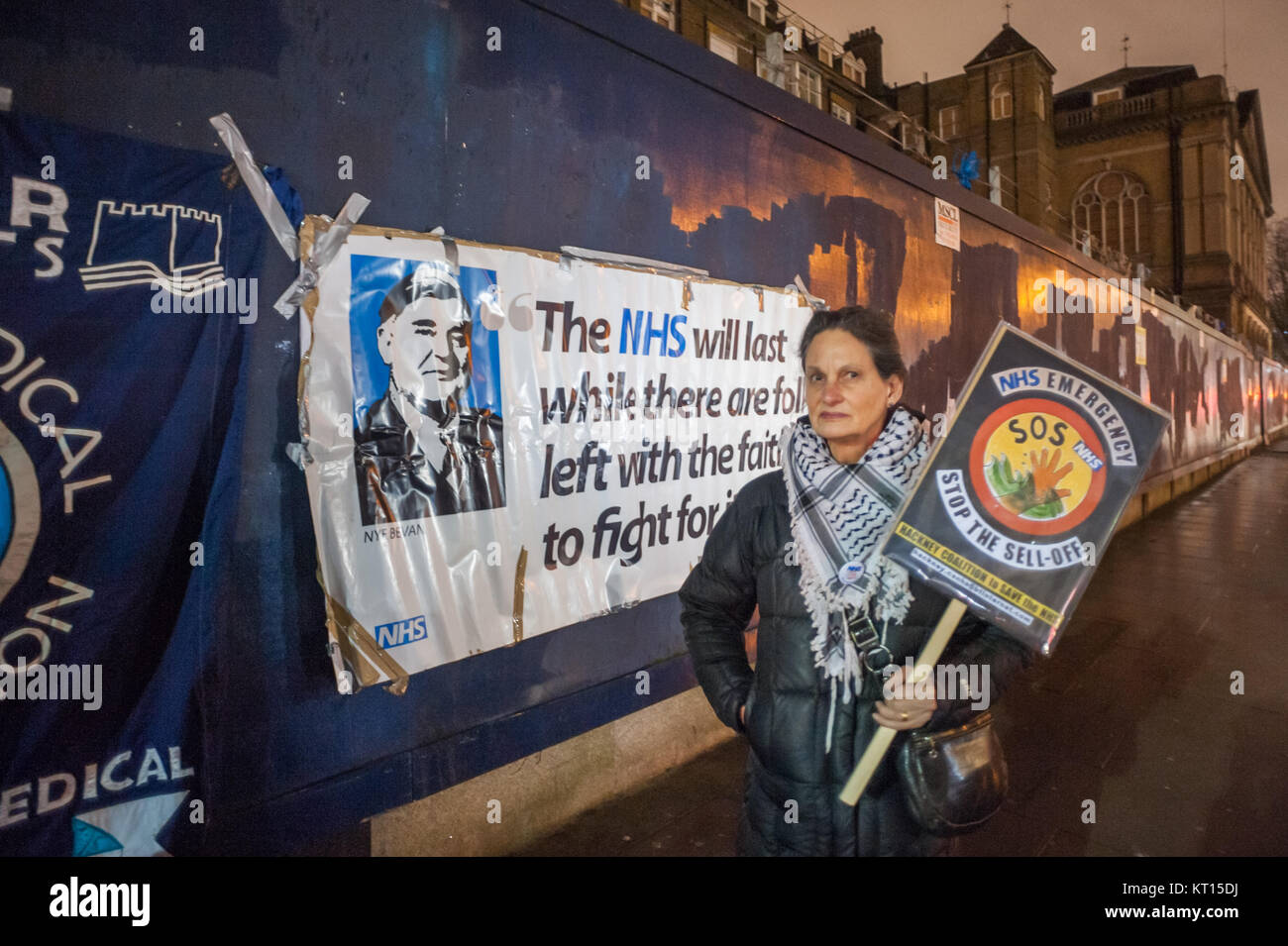 Woman with placard in front of Nye Bevan banner at Christmas protest outside old Royal London Hospital supporting - Stock Image