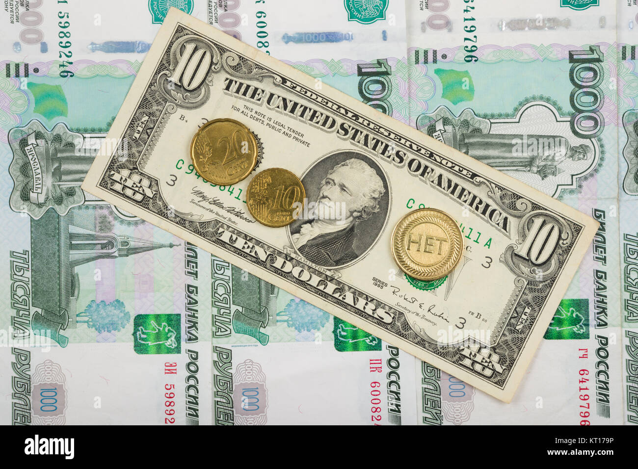 The coin with the inscription no and the euro are on the bill of ten dollars which lies on a pile of thousand-Russian Stock Photo