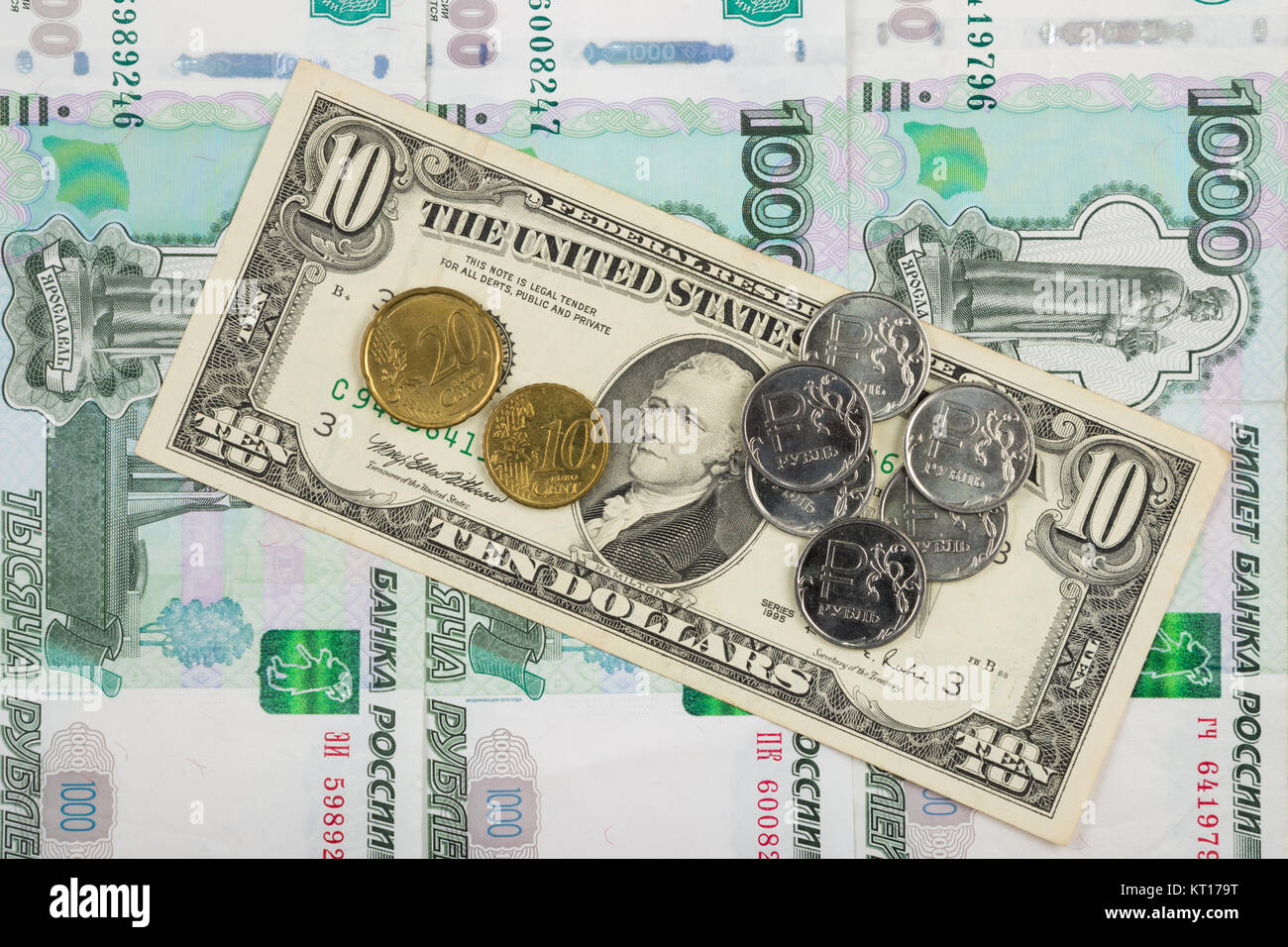 Coins ruble and the euro are on the bill of ten dollars which lies on a pile of thousand-Russian banknotes Stock Photo