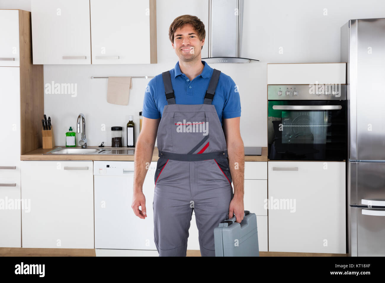 Happy Young Worker Holding Toolbox - Stock Image