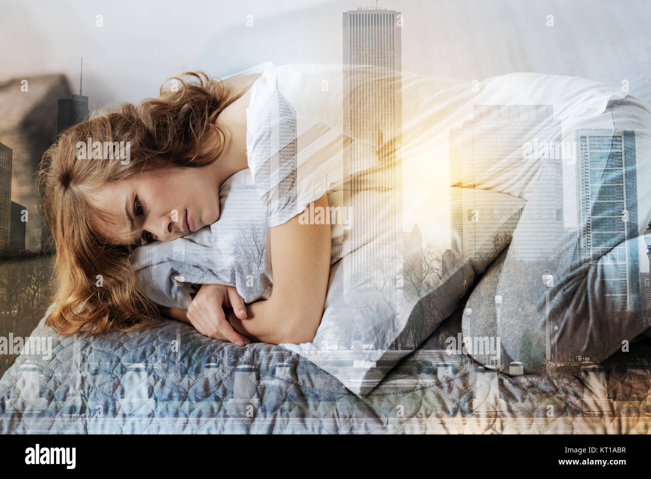Sick female person lying on her bed - Stock Image