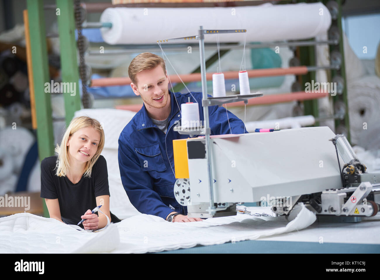 Seamstress is new assigned to a machine in a textile factory, the foreman explains something Stock Photo