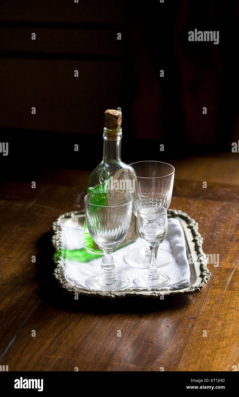 Bottle of Chartreuse and glasses in a darkened corner. - Stock Image