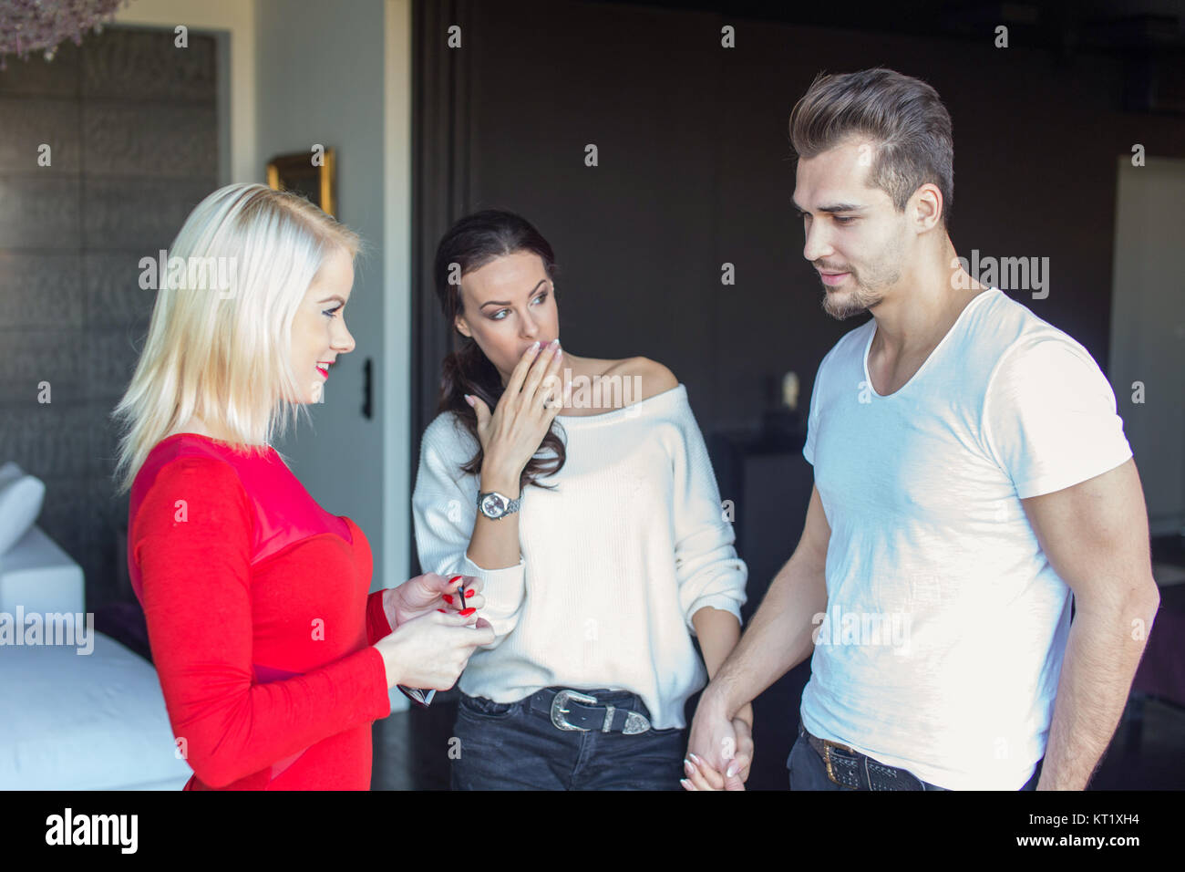Girlfriend shocked on disloyal boyfriend flirting with blonde woman in red dress, indoors - Stock Image
