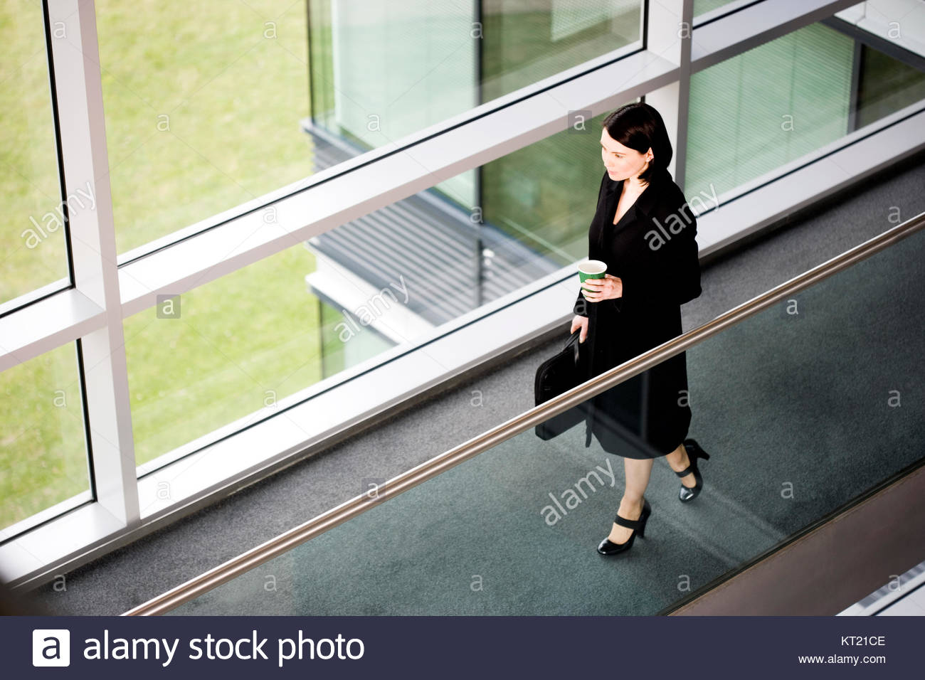 Businesswoman in modern office building, arriving for work - Stock Image