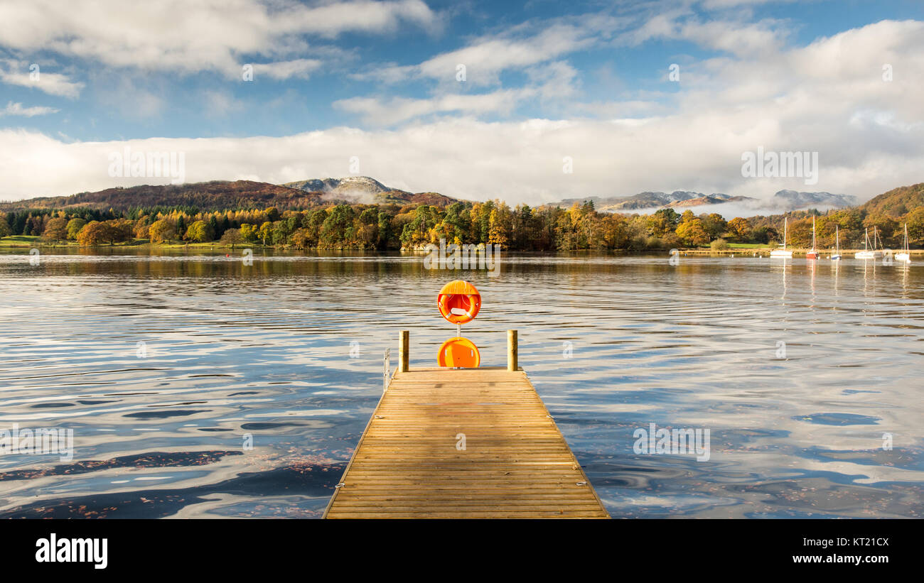 Sun shines on a pier at Ambleside on Windermere lake, under the mountains of Langdale and autumn woodland in England's - Stock Image