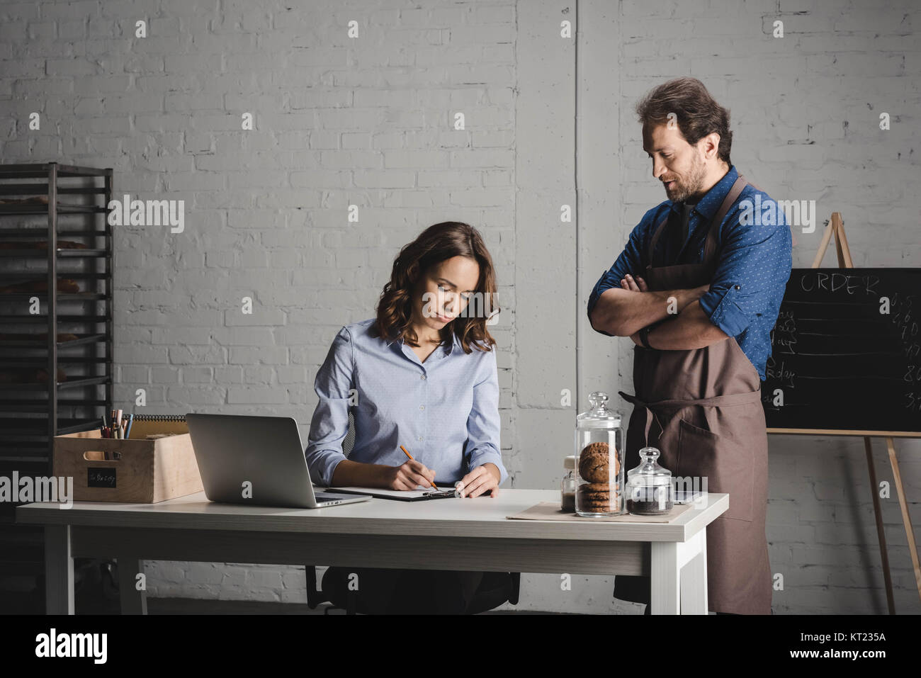 Bakers discussing and making notes - Stock Image