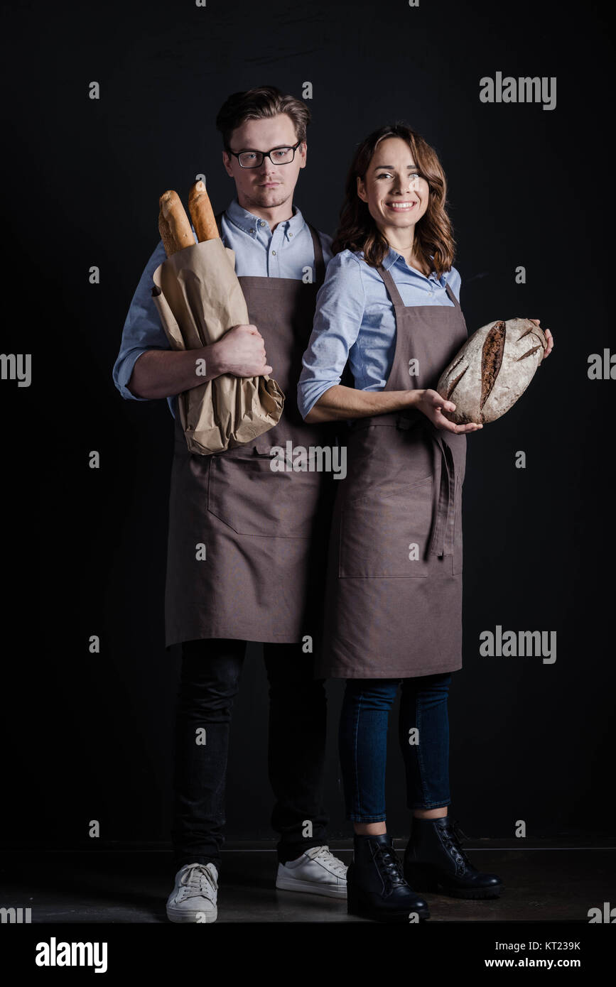 Bakers holding bread - Stock Image