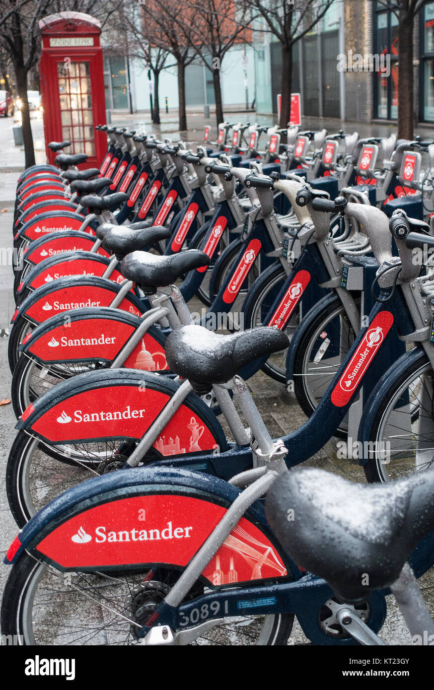 Lines of Red Rental Bicycles with Snow on Saddles Sponsored by Santander near Tower Bridge London England United Stock Photo