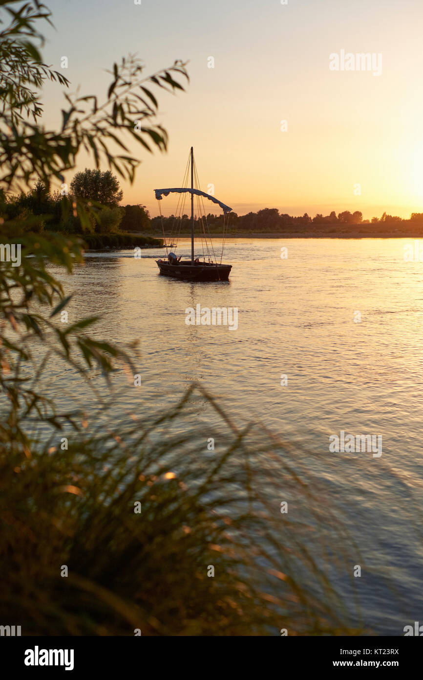 A traditional Loire River flat bottomed wooden Gabares saling boat at sunset in the Loire Valley near Amboise France. - Stock Image