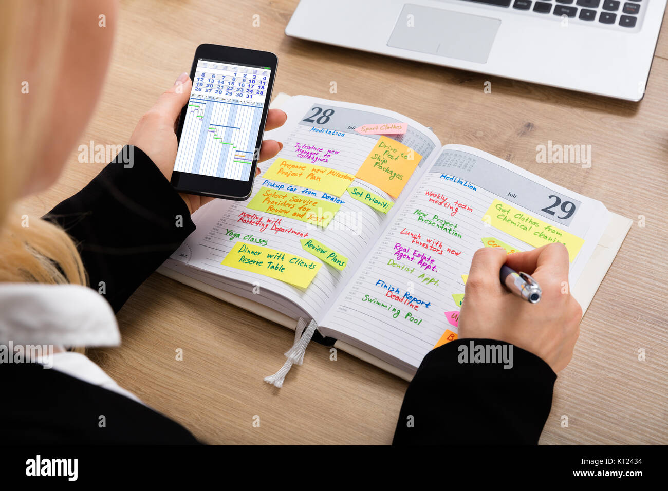 Businesswoman With Mobilephone Writing Schedule In Diary Stock Photo
