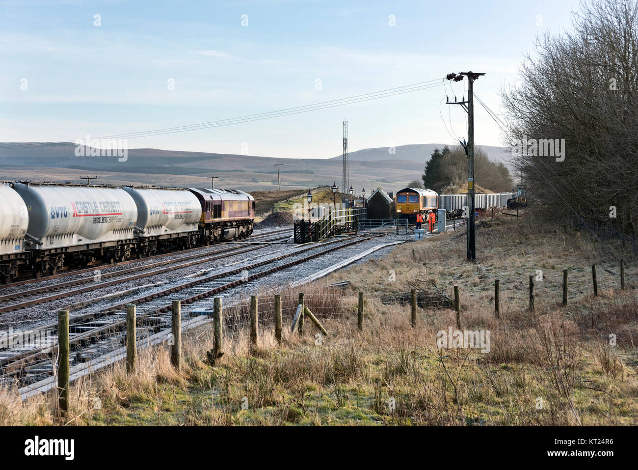 Cement waggon train drawn by Class 66 locomotive passes another train loading stone in the siding at Ribblehead - Stock Image