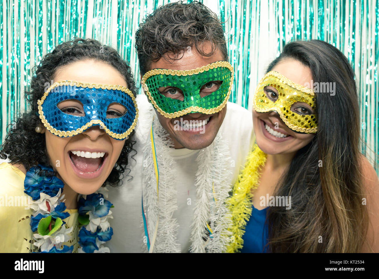 Multi ethnic group of friends is wearing Carnaval masks. Happiness and euphoria. Partygoers are having fun partying, - Stock Image