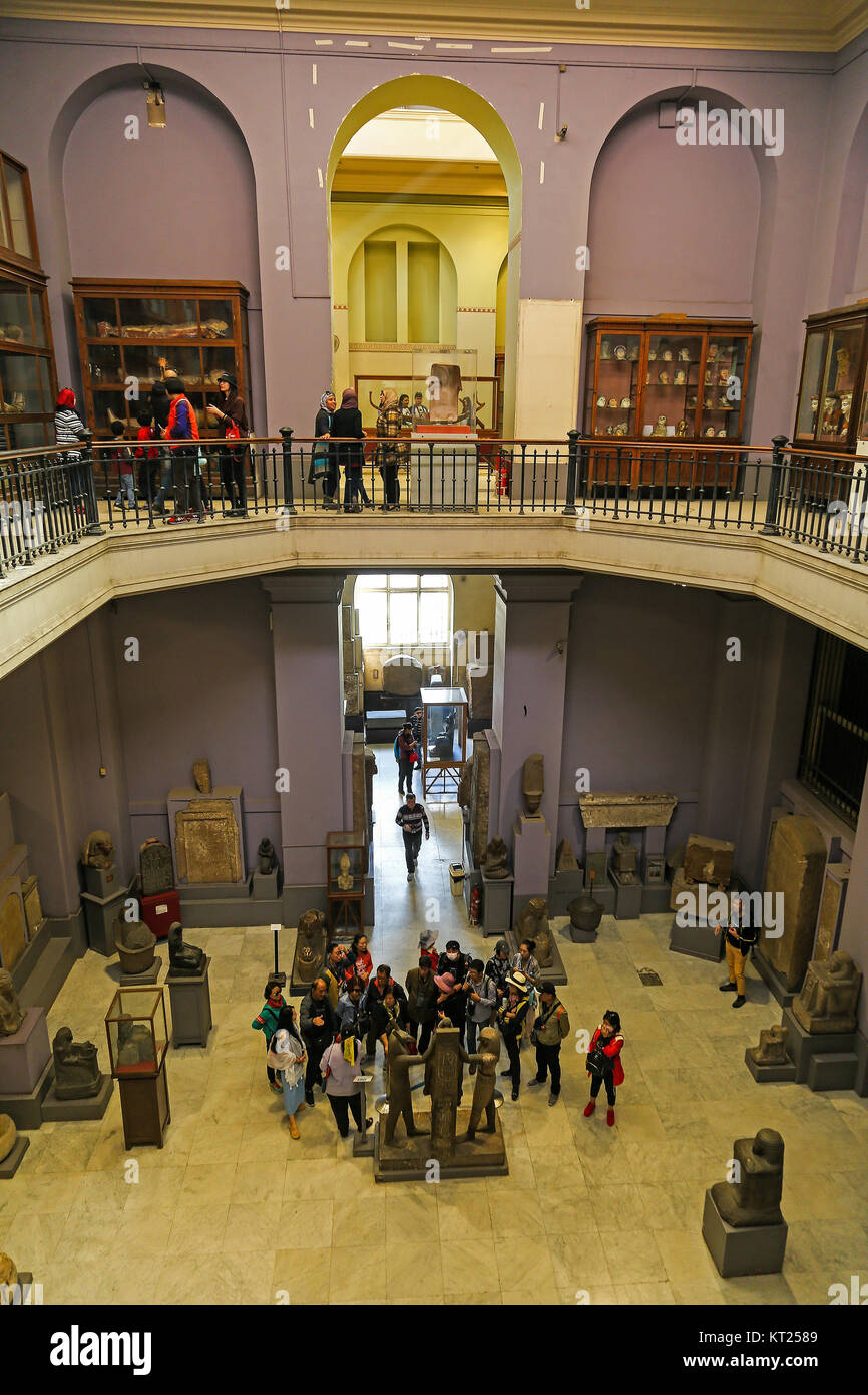 People looking at the artefacts on display inside the Egyptian Museum of Antiquities, Cairo, Egypt - Stock Image